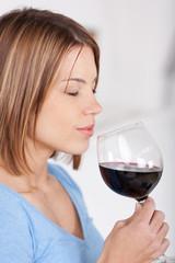 frau genießt rotwein mit geschlossenen augen