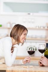 lächelnde frau in der küche stößt mit rotwein an