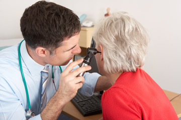 British doctor examining senior woman's ear