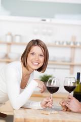 lachende frau mit rotwein in der küche