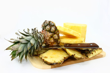 Fresh Pineapple Pieces And Knife On A Cutting Board
