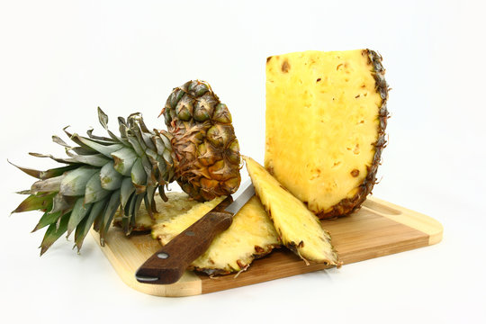 Fresh Pineapple Being Cut On A Wooden Board