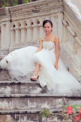 women in white dress bride sitting on stairway