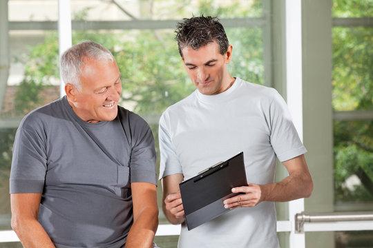 Fitnesstrainer redet mit Senioren