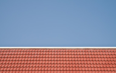 Red roof on blue sky background.