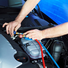 Motor mechanic works on engine bay with air handling unit