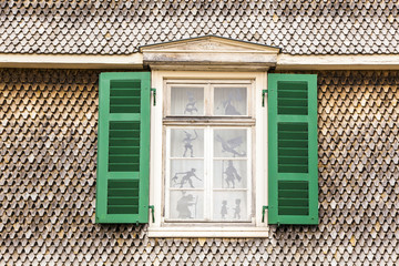 old wooden facade with open window and figures in the glass