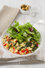 omelet with vegetables and salad on the plate