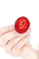 woman's hand showing a halved ( bitten ) fresh strawberry,