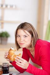 frau genießt ihr croissant zum frühstück