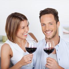 lachendes paar stößt mit rotwein an