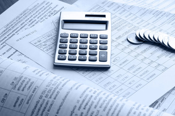A line of coins and a calculator on business papers