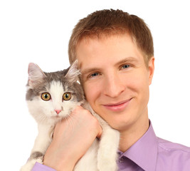 Smiling young man holds surprised cat isolated on white