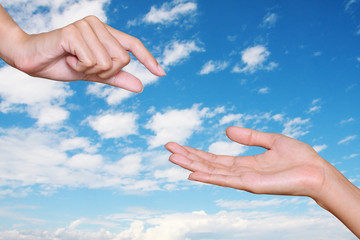 hand give something to another hand with blue sky background