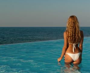 Sexy woman in white bikini standing at infinity pool