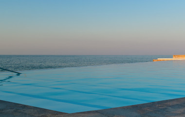 Infinity pool on the beach at sunset