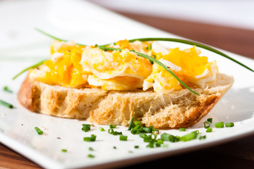 scrambled eggs canape garnished with chives