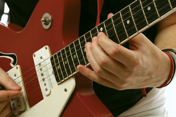 Closeup of a guitarist playing, focus on his hand
