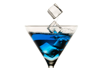 Dropping ice cubes into martini glasses on white background