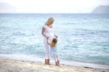 Foto op Aluminium Cyprus junge schwangere mutter mit ihrer tochter am strand