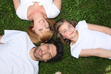 Family wearing white lying in the grass