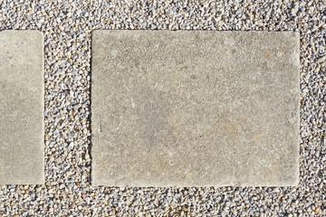 Concrete paving slap with gravel surround.