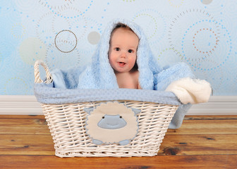 cute baby boy sitting in basket with blanket on head