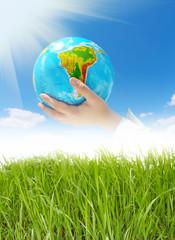 globe in hands under blue sky