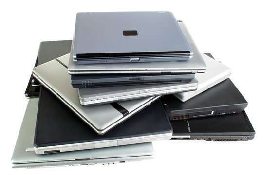 Stack of used laptop computers, isolated on white