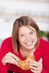 lachende frau isst ein croissant