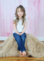 adorable little girl posing on brown fur rug