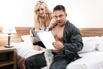 Young sexy couple reading together a magazine in their bedroom