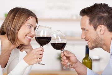 glückliches paar stößt mit einem glas wein an