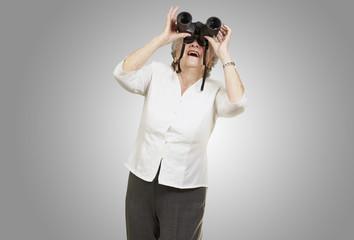 portrait of senior woman looking through a binoculars against a