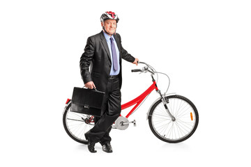 Full length portrait of a senior businessman posing next to a bi
