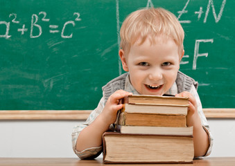 Cheerful smiling   child resting on a stack of books