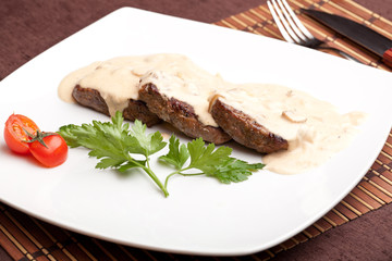 Roasted meat under white sauce