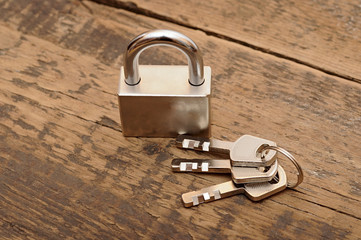 padlock and keys on wooden table