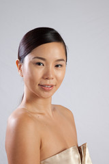 Pretty Asian woman with bare shoulders and pleasing expression