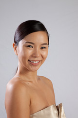 Pretty Asian woman with bare shoulders and happy smile