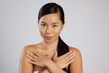 Pretty asian woman with hands across her chest