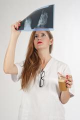 Doctora joven analizando una radiografía tomando café.