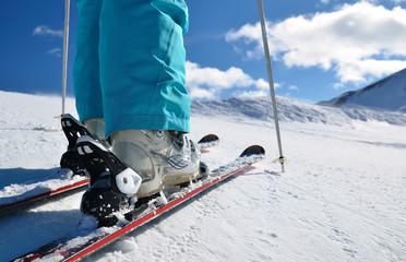 Fototapeta woman's legs in ski boots, standing on skis obraz