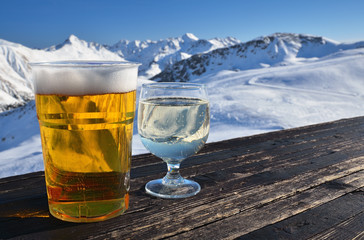 Glasses with beer and wine on a table in alpine mountain cafe