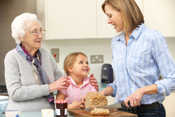 Multi-generation family preparing food in kitchen
