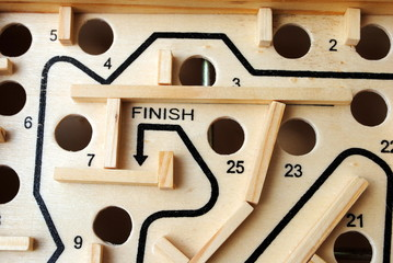 write finish in a wooden labyrinth with holes on the path