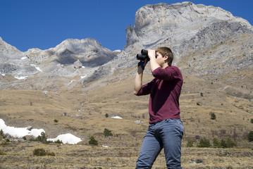 Mountain hiker looking through binoculars
