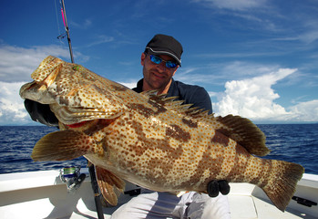 Happy  fisherman holding a grouper