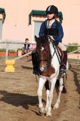 bambina a lezione di equitazione