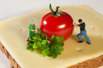 Miniatur Arbeiter bereiten einen Pausen Snack zu